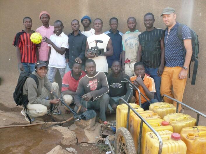 Filmteamet. Trond Waage i oransje bukser. Nede til venstre Adamou Amadou, tidligere student ved visuelle kulturstudier ved UiT, antropolog og lydmann i produksjonen. Adamou er fra Ngaoundéré. Alle de andre på bildet kjemper daglig om jobben med å trille vann i boligkvarteret.