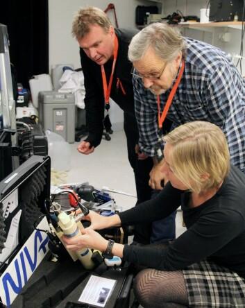 Forskningsledere i NIVA, Bert van Bavel (t.v.) og Kai Sørensen, demonstrerer instrumentene som skal tas i bruk på «Kon-Tiki 2» til ekspedisjonens chief scientist Cecilie Mauritzen. (Foto: NIVA)