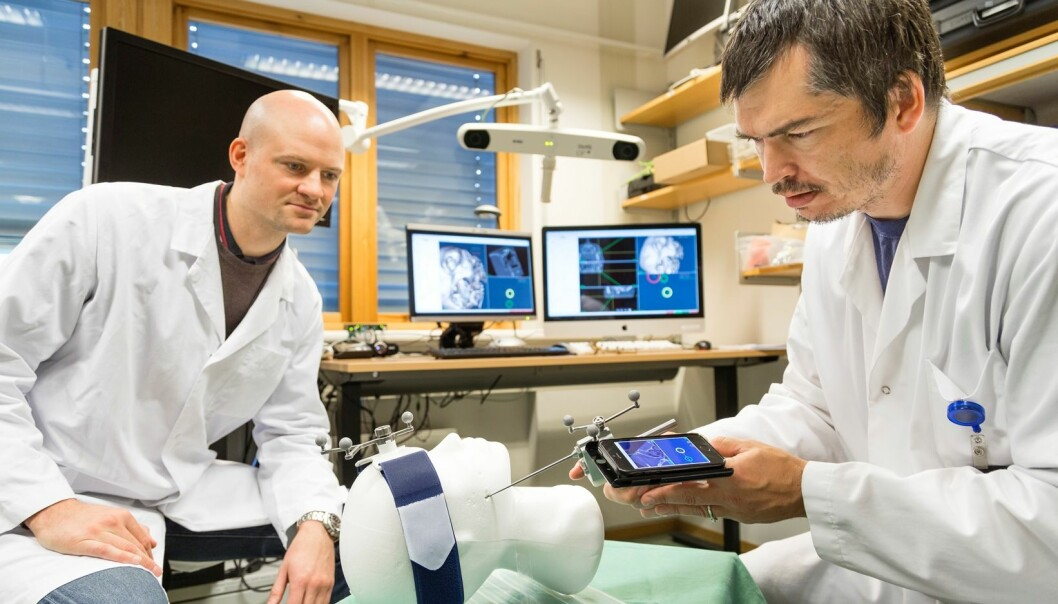 The two SINTEF technologists Christian Askeland (right) and Jon Eiesland seen here testing the new needle guidance system in the laboratory. (Photo: Thor Nielsen, SINTEF)