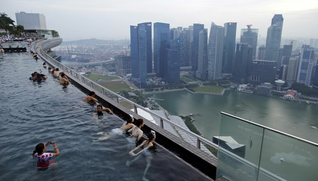 Turister bader i bassenget på taket av hotellet Marina Bay Sands i Singapore. (Foto: Edgar Su, Reuters, NTB Scanpix)