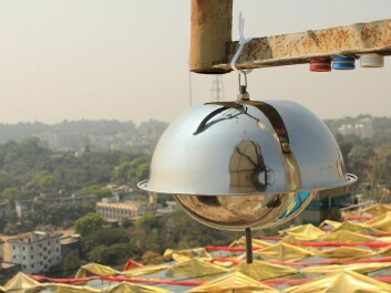"""The image shows air samplers in the city of Chittagong in Bangladesh. The large """"metal dome"""" collects air samples for analysis of environmental pollutants, while the three small cylinders measure nitrogen dioxide (blue), sulfur dioxide (red) and ozone (white). (Photo: Scott Randall, NILU)"""