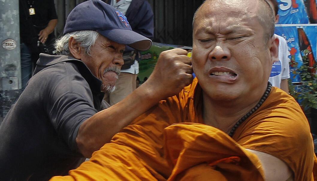 Vold og slåssing er et menneskelig fenomen. Her går en demonstrant i Bangkok løs på en munk som klagde på demonstrasjonen. (Foto: Chaiwat Subprasom/Reuters)