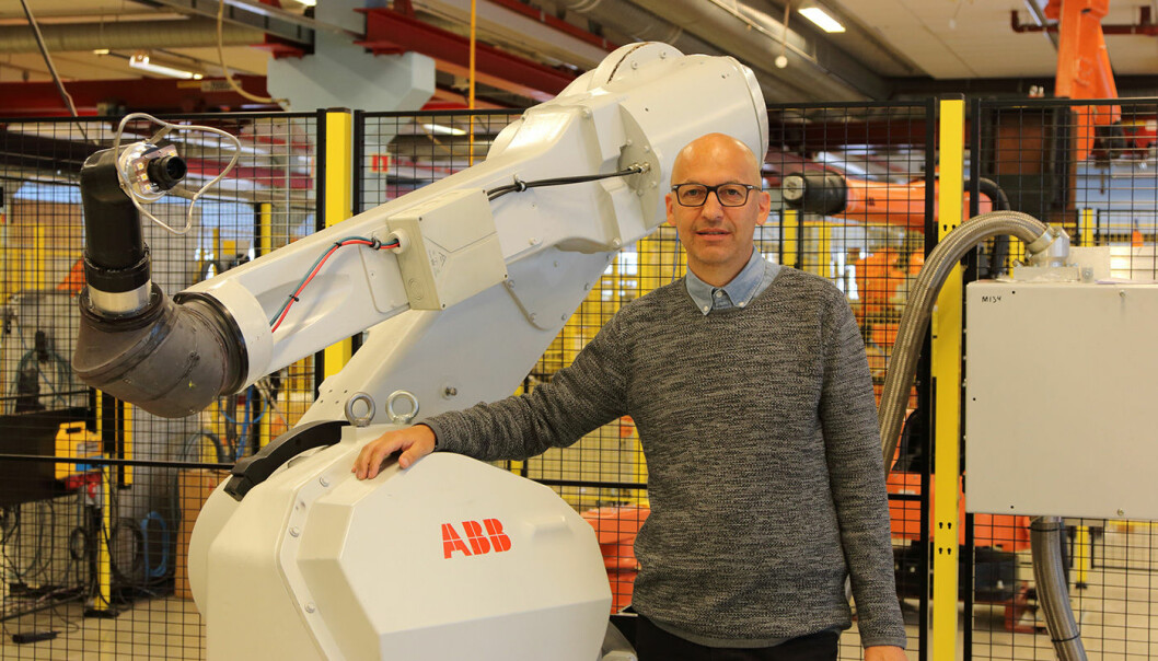Morten Mossige in front of a ABB robot. Morten Mossige's Industrial PhD at the University of Stavanger is the first of its kind at ABB in Norway. (Photo: Leiv Gunnar Lie, UiS)