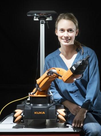 Forsker Marianne Bakken har fått denne robotarmen til bevege seg så raskt at den aldri kolliderer med henne, uansett hvilke bevegelser hun gjør.  (Foto: Sintef IKT)