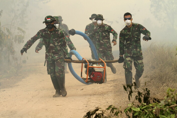 Indonesiske soldater bærer en vannpumpe i de brannherjede skogene på Sumarta i Indonesia. (Foto: Antara foto, Reuters)
