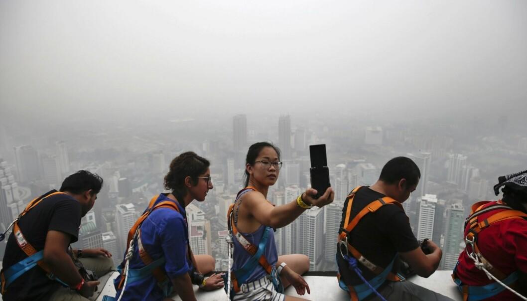 En kvinnelig turist tar en selfie på toppen av et høyt bygg i Kuala Lumpur i Malaysia i begynnelsen av oktober. Skogbranntåke ligger tykt over Kuala Lumpur, Singapore og andre steder i området. (Foto: Fazry Ismail/Epa)