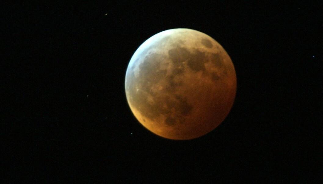 Ved total måneformørkelse farges månen rød. De røde delene av sollyset når fram til og reflekteres fra månen, selv om jorda ligger i veien. Fargenyansen avhenger av hvor mye støv det er i jordatmosfæren.  (Foto: Gorm Kallestad, NTB scanpix)