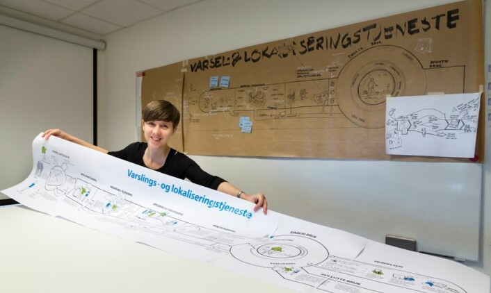 Silje Bøthun er en av forskerne som forhåpentligvis skal gjøre det enklere for kommunene å ta i bruk GPS for folk med demens. Her står hun med en stor illustrasjon fra forskningsprosjektet. (Foto: (Illustrasjon: Splinter/Sintef))
