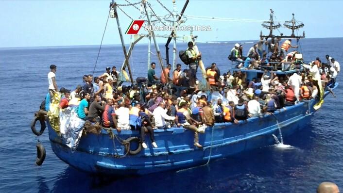 Menneskene i denne båten på vei fra Libya til Italia, ble reddet av den italienske kystvakten 23. august i år. Flere enn 60 000 flyktninger og immigranter kom til hvert av landene Helles og Italia første halvår i 2015. De fleste kom med båt over Middelhavet.  (Foto: (Foto fra Italias kystvakt / NTB))