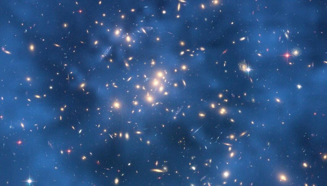 Mørk materie er usynlig, men kan registreres gjennom såkalt gravitasjonslinsing. Her ser vi den mørke materien som en blå ring rundt galaksen CL0024+17. (Foto: Jee og Ford mfl, NASA/ESA)