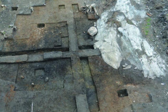 Gulvet i den ovale tuften. Sees som et ovalt, mørkt lag. De skarpe, rette kantene er skapt av arkeologene som graver ut restene etter bygningen.  Foto: Kulturhistorisk museum.