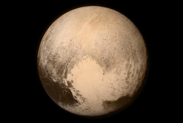 """Dette bildet av Pluto ble tatt 13. juli 2015 klokka 22 norsk tid, 16 timer før romsonden New Horizons passerte nærmest dvergkloden i en avstand på 12 500 kilometer. Her er avstanden hele 768 000 kilometer, rundt dobbelt så stor som avstanden mellom jorda og månen. Bildet er opprinnelig tatt i svart-hvitt med kameraet  Long Range Reconnaissance Imager (LORRI), men er tilført fargeinformasjon med lavere oppløsning fra kameraet Ralph. Bildet domineres av et stort, lyst området som kalles """"hjertet"""". Det måler rundt 1600 kilometer tvers over. På hver side ligger mørkere terreng ved Plutos ekvator. Mye av """"hjertet"""" framstår som jevnt. Det kan tyde på at det er et ungt terreng hvor geologiske prosesser fortsatt pågår, siden det ennå ikke har fått arr av meteorittnedslag. (Foto:  NASA/APL/SwRI)"""