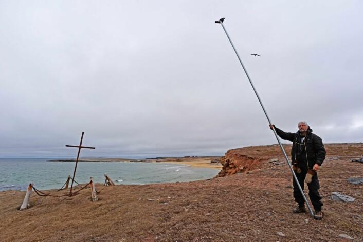 På plass ved korset i Nordhamna. Dag er veldig fornøyd med det lange røret. Med dette får han god høyde til å ta oversiktsbilder med fjernutløser. Ved å ta bilder fra forskjellige vinkler så vil vi kunne lage dreibare 3d-modeller både neset og strukturene.  (Foto: Arild S. Vivås/Sysselmannen på Svalbard)