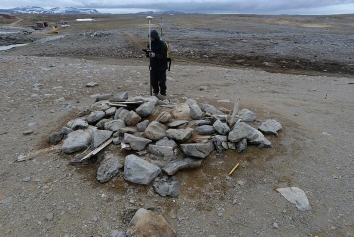 Arild måler inn den store graven på Gravodden. Graven er minst tre ganger så stor som de vanlige fangstmennsgravene. Dette indikerer at det her ligger flere individer begravd, og vi tror at det var i denne graven at Tobiesen gjengravde levningene etter de minst 14 pomorene.  (Foto: Dag Nævestad/Sysselmannen på Svalbard)