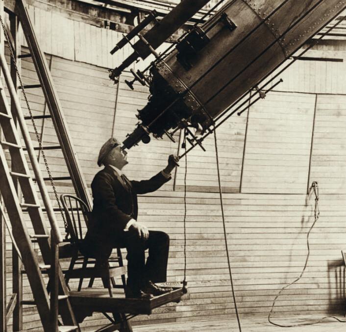 Percival Lowell observerer planeten Venus i 1914 gjennom 24-tommers linseteleskopet ved observatoriet han grunnla i Flagstaff, Arizona. Lowell var intenst opptatt av å finne den mystiske kjempeplaneten Planet X utenfor Neptuns bane, ikke minst for å gjenopprette kollegers faglige tillit til ham. På begynnelsen av 1900-tallet hadde han nemlig lansert idéen om at de imaginære kanalene på planeten Mars var laget av intelligente skapninger. (Foto: Ukjent/Public domain)