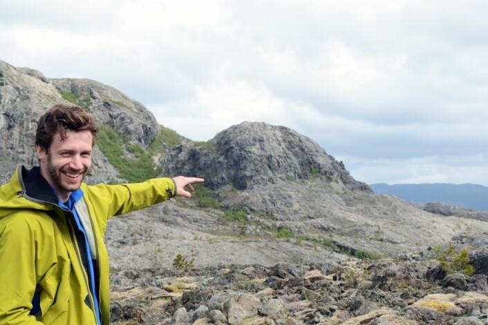 Forsker Fredrik Høgaas peker ut strandlinja i fjellet i bakgrunnen. Frost og sjøis har arbeidet hardt for å lage linja. (Foto: Gudmund Løvø)