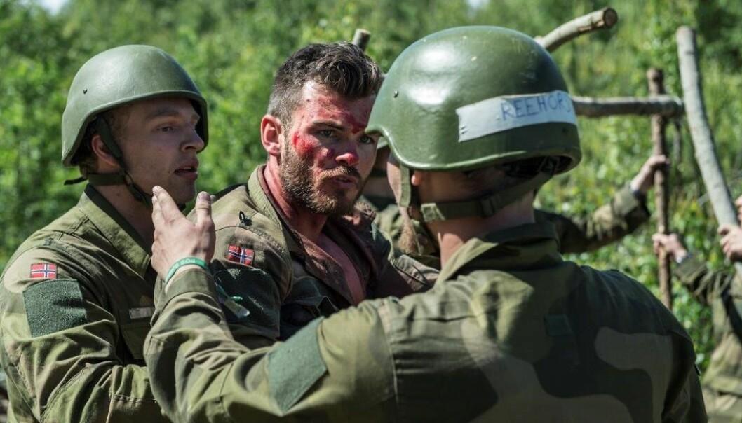 "To aspiranter prøver å håndtere en ""skadd"" soldat"" under opptak til Forsvarets lederutdanning.  (Foto: Forsvaret)"