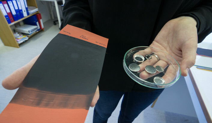 Til venstre holder Hanne Andersen et flak av silisium og karbon. Det skal skjæres opp i rundinger som passer inn i batterihylstrene hun holder i den andre hånden. (Foto: Arnfinn Christensen, forskning.no)