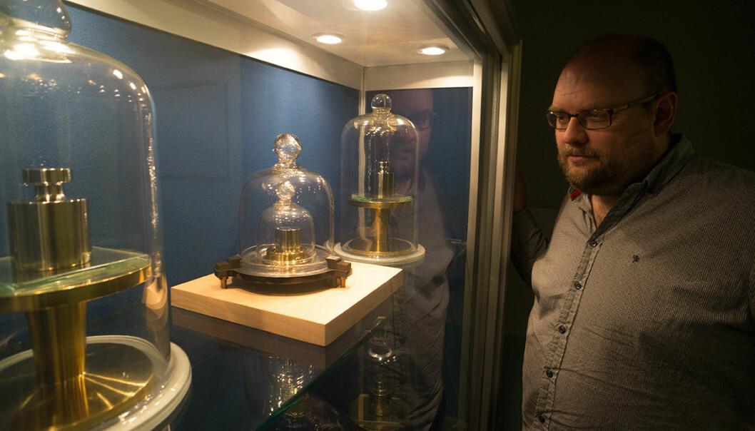 Harald Hauglin betrakter den norske standardkiloen i midten på bildet. Kiloloddet er den siste fysiske enkeltgjenstanden som definerer en måleenhet. Utviklingen går mot å bruke fysiske naturkonstanter, som for eksempel lyshastigheten og energinivåer i atomer. (Foto: Arnfinn Christensen, forskning.no)