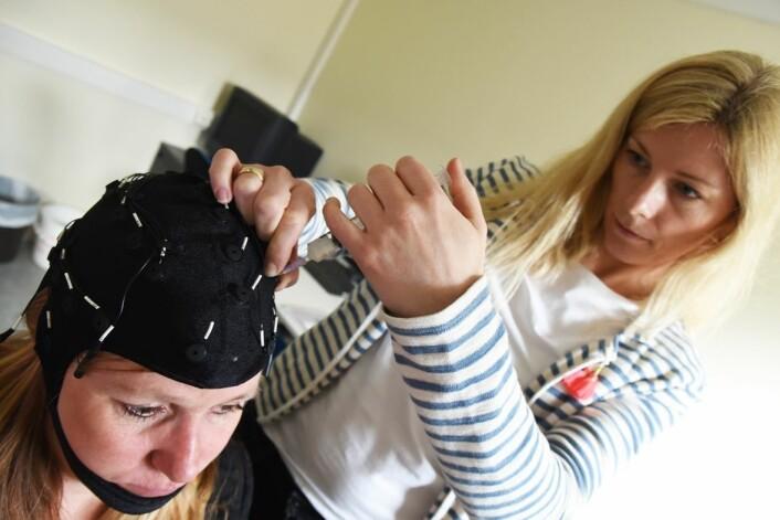 To av fem pasienter med langvarig bevissthetsforstyrrelse etter akutt hjerneskade får feil diagnose fordi tegn til bevissthet overses. Her demonstrerer nevropsykolog Solveig Lægreid Hauger metoden, som er basert på EEG, på forsker Marianne Løvstad (til venstre). (Foto: Ola Sæther)