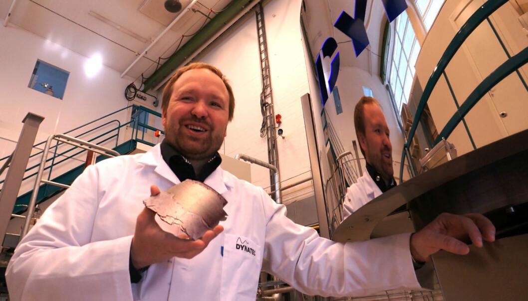 Den nye utgaven av sentrifugen til firmaet Dynatec kan hente ut rent silisium uten å avkjøle anlegget. Dermed produserer det silisium rundt 40 ganger raskere enn et tradisjonelt anlegg. Forskningsleder Werner Filtvedt i Dynatec viser fram et stykke silisium som er hentet ut fra den krumme innerveggen av sentrifugen bak ham. (Foto: Arnfinn Christensen, forskning.no)