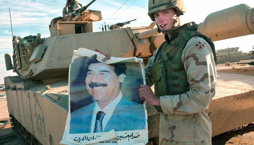En amerikansk soldat fra 2003 viser frem en plakat av den avsatte irakiske presidenten Saddam Hussein. US Army Research Lab påpeker at den nye, matematiske logikken, som er utviklet ved Universitetet i Oslo, kan bedre det amerikanske etterretningsarbeidet. (Foto: Stefan Zaklin, EPA)