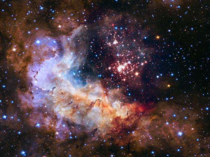 Stjerneklyngen Westerlund 2 sett av romteleskopet Hubble. Westerlund 2 ligger i stjernebildet Carina rundt 20 000 lysår fra jorda og inneholder cirka 3000 stjerner. Her antennes nye stjerner, synlige i hvitt og blått. Røde punkter er stjerneembryoer som ennå ikke har blitt tent.  (Foto: NASA, ESA, the Hubble Heritage Team (STScI/AURA), A. Nota (ESA/STScI) and the Westerlund 2 Science Team)