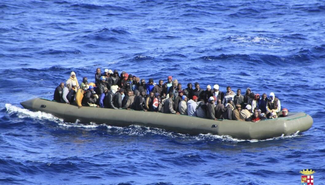 En båt med flyktninger som etter en lang reise over Middelhavet er i ferd med å bli reddet av det italienske marineskipet San Marco utenfor kysten av Sicilia.  (Foto: Reuters)