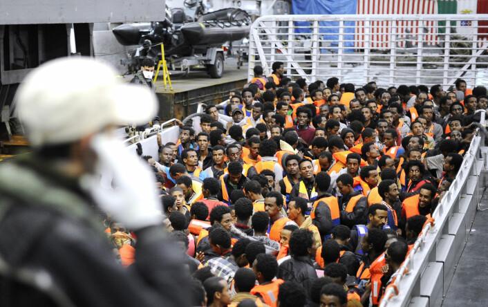 Flyktninger fra afrikanske land sør for Sahara står på et av den italienske marinens skip etter å ha blitt reddet i internasjonalt farvann mellom Italia og Libya 14. mai i fjor. Skipet San Giorgio er et av fem skip som er involvert i lete- og redningsoperasjonene som kalles Mare Nostrum – Vårt hav. (Foto: Reuters)
