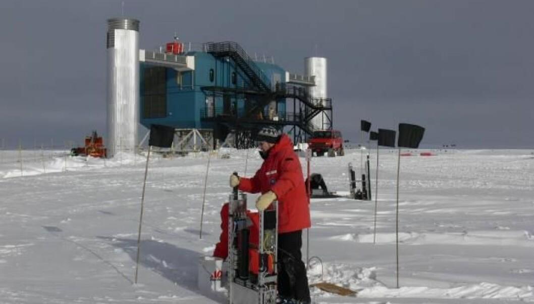 Jason Koskinen fra Københavns Universitet foran den kjempestore IceCube-detektoren på Sydpolen. Den leter etter nøytrinoer med instrumenter dypt nede i isen. Alle data fra instrumentene kommer opp gjennom de to «tårnene» og inn til et datasenter.  (Foto: T. Waldemaier)