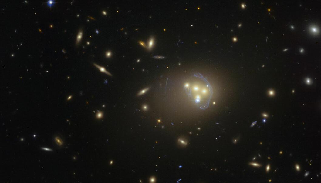 Galaksehopen Abell 3827 ligger omtrent midt i bildet. Legg merke til at lyset fra en fjern galakse må gjennom denne galaksekollisjonen, og selve lyset blir bøyd og strukket på grunn av de kraftige gravitasjonsfeltene. Du ser noe av lyset som en avlang banan til høyre. (Foto: ESO)