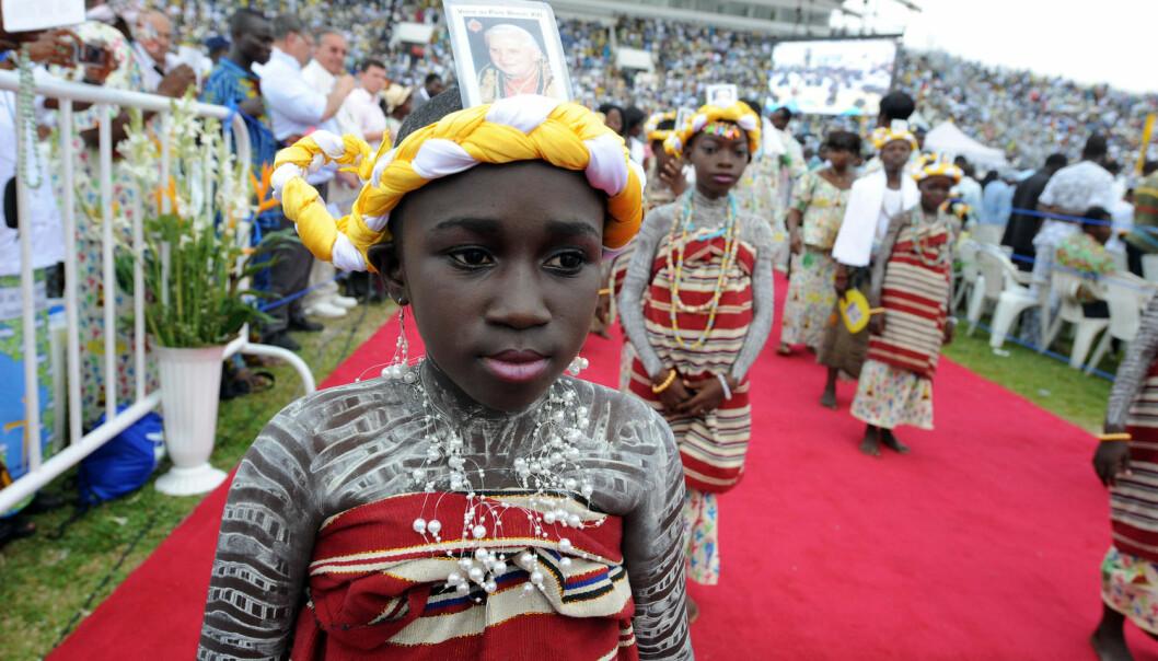 Unge jenter i Benin hilste paven velkommen med bilder av ham i hodebåndene da den daværende paven kom på besøk til det vestafrikanske landet i 2011. Benin regnes som opprinnelsessted til tradisjonell voodoo-religion, men får i likhet med mange andre afrikanske land stadig flere kristne innbyggere. Kristendommen her blir på sin side påvirket av spirituelle uttrykksformer.  (Foto: AFP/NTB)