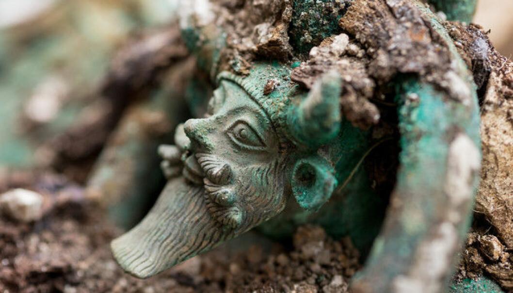 En stor bronsekjele er funnet i graven. Håndtakene på kjelen forestiller den gresk guden Akheloos.  (Foto: Denis Gliksman, Inrap)