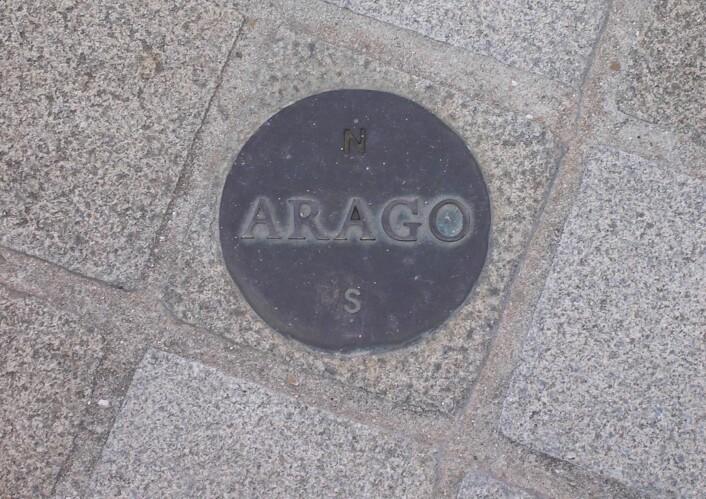 """Langs Paris-meridianan er det plassert 135 slike medaljonger. Dette er en av de som ligger rett ved Louvre-pyramiden. N peker mot nord, S mot sør. Arogo er til minne om astronomen som også var statsminister i Frankrike i halvannen måned på forsommeren i 1848. (Foto: Poulpy, <a href=""""http://creativecommons.org/licenses/by-sa/3.0/deed.en"""" target=""""_blank"""">Creative Commons</a>)"""