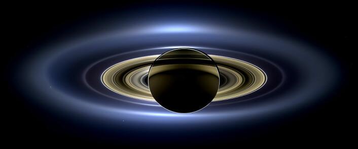 Saturn sett fra Cassini-sonden. Solen er bak Saturn, og gir planeten et dramatisk skjær. E-ringen, som blant annet består av partikler fra Enceladus, er den ytterste ringen vi kan se på dette bildet. (Foto: NASA)