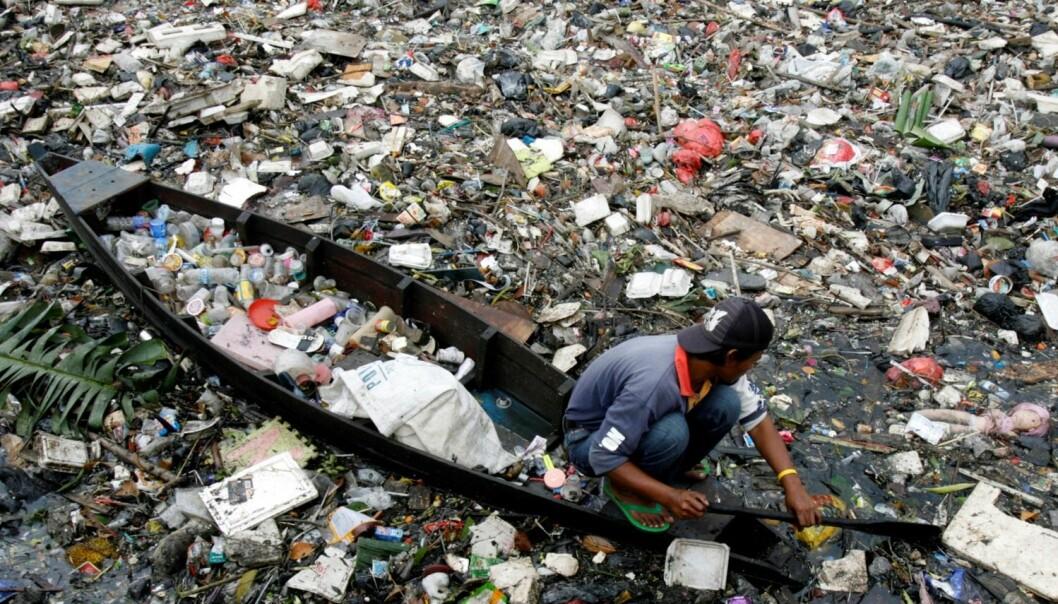 En mann staker seg vei gjennom søppelet på en elv i Jakarta, Indonesia. Elver er en av kanalene som fører plast til sjøen. Indonesia er sannsynligvis det landet som sørger for nest mest plastsøppel på avveie. Bare Kina sender ut mer. (Foto: Reuters)
