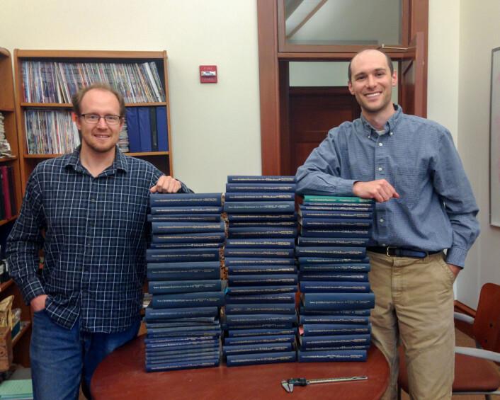 To av forskerne bak studien, Jonathan Payne (t.h.) og Noel Heim, med stabelen av storverket Treatise on Invertebrate Paleontology, som de brukte for å vise at Copes lov gjelder for sjødyr. (Foto: Med tillatelse fra Noel Heim)