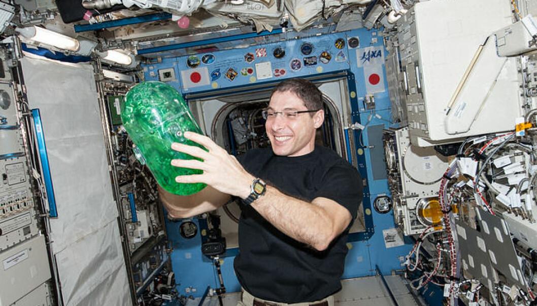 En av astronautene leker med vanntanken i Spheres Slosh-eksperimentet. Som navnet tilsier handler det om skvalping.  (Foto: NASA)