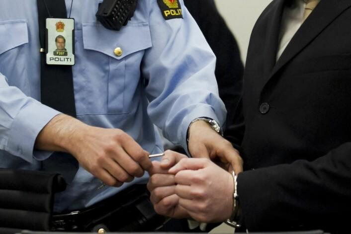 16. april 2012: Anders Behring Breivik får låst opp håndjernet av politiet inne i sal 250 i Oslo Tinghus, på rettssakens første dag.  (Foto: Heiko Junge/NTB Scanpix)