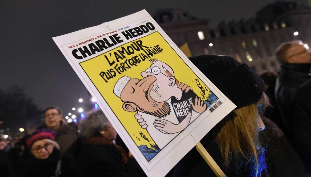 En kvinne holder en plakat av en Charlie Hebdo-forside med teksten Kjærlighet sterkere enn hat. Bildet ble tatt under markeringen på Place de la Republique i Paris 7. januar 2015, etter angrepet på redaksjonen til satiremagasinet Charlie Hebdo der 12 mennesker ble drept.   (Foto: Scanpix, Dominique Faget)