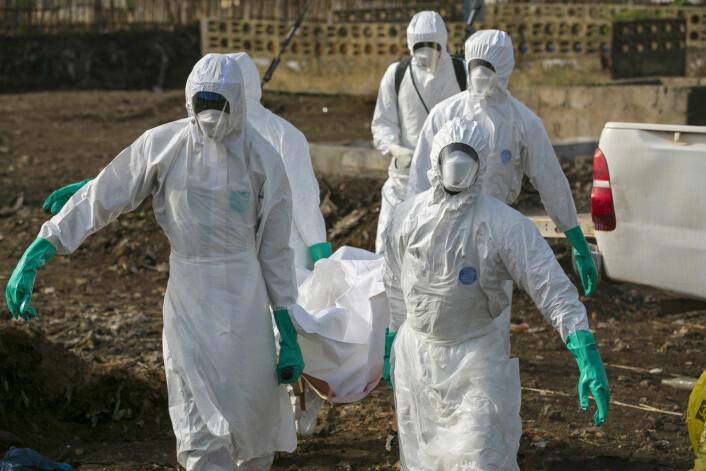 Helsearbeidere bærer en båre med liket av en person som antas å ha dødd av ebola. Nå er en ny og lovende vaksine utviklet. Dersom alt går som det skal kan den være ute på markedet til neste år.   (Foto: Baz Ratner, Reuters, NTB scanpix)