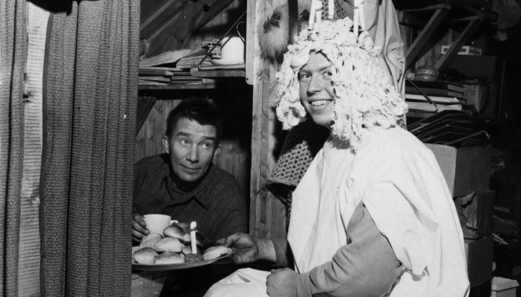 Sankta Lucia tar ekspedisjonssjefen på senga med ferske boller. Året er 1950. Stedet er Antarktis.  (Foto: Norsk Polarinstitutts bildearkiv)