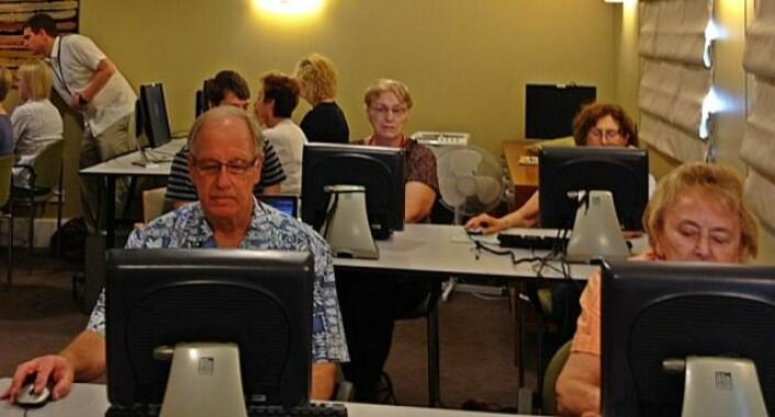 Flere eldre sitter sammen og spiller hjernetreningsspill med veiledere tilstede. (Foto: University of Sydney)