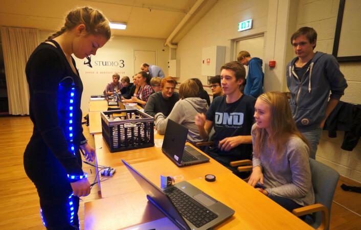 Hver danser får hjelp av tre programmerere, slik at lyset i drakten tenner til riktig tid og med riktig farge. Fra venstre: Danseren Nora Kveum, programmererne Kristoffer Nyvoll, Idunn Haavengen og Even Thonhaugen Røraas. (Foto: Arnfinn Christensen, forskning.no)