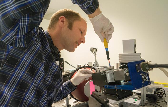 Ivar Baarstad med et hyperspektralt kamera under produksjon i Norsk Elektro Optikks lokaler ved Skedsmokorset. (Foto: Arnfinn Christensen, forskning.no)