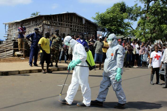 Helsearbeidere desinfiserer seg selv etter å ha hentet en død kvinne i Freetown i SierraLeone. (Foto: Josephus Olu-Mammah, Reuters)