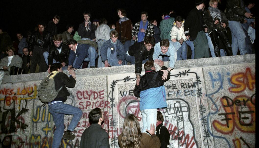 Tusenvis av mennesker krabbet opp på muren ved Brandenburger Tor i Vest-Berlin fredag 9. november 1989.  (Foto: Scanpix, Jørn H. Moen)