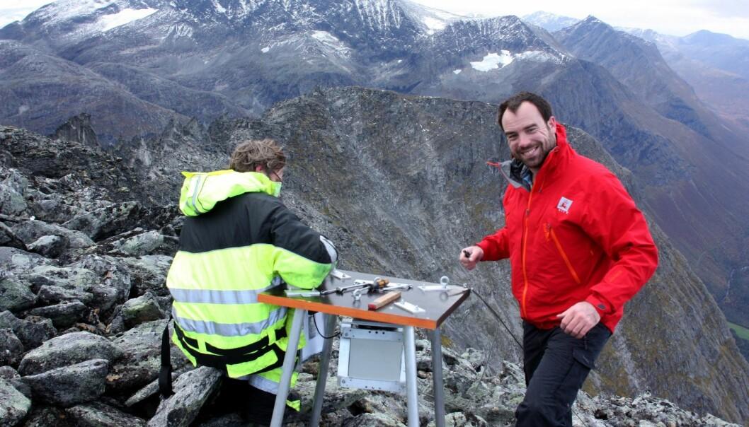 John Anders Dahl fra NGU og Odd Are Jensen fra NVE monterer kamera på toppen av Gråfonnfjellet i Åndalsnes. (Foto: Freddy Yugsi Molina, NGU)