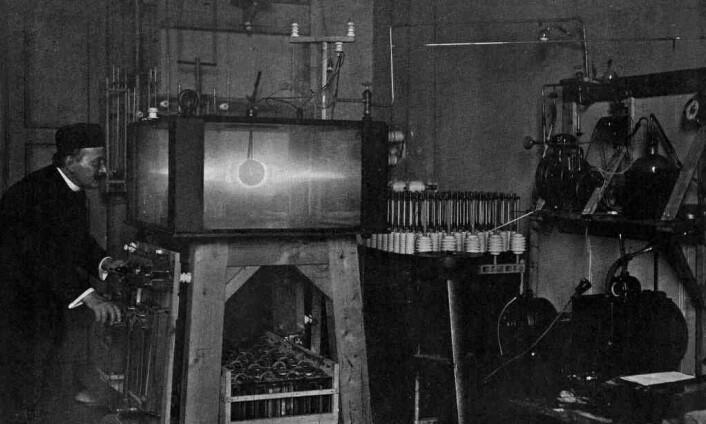 """Kristian Birkeland med terrella. Glasskassen hadde et volum på 320 liter. Gulv og tak var laget av 12 mm stålplater, søylene mellom dem er av bronse, og glassplatene er 3 cm tykke. (Foto: Fra Kristian Birkelands bokverk """"The Norwegian Aurora Polaris Expedition 1902-1903"""", publisert i 1913)"""