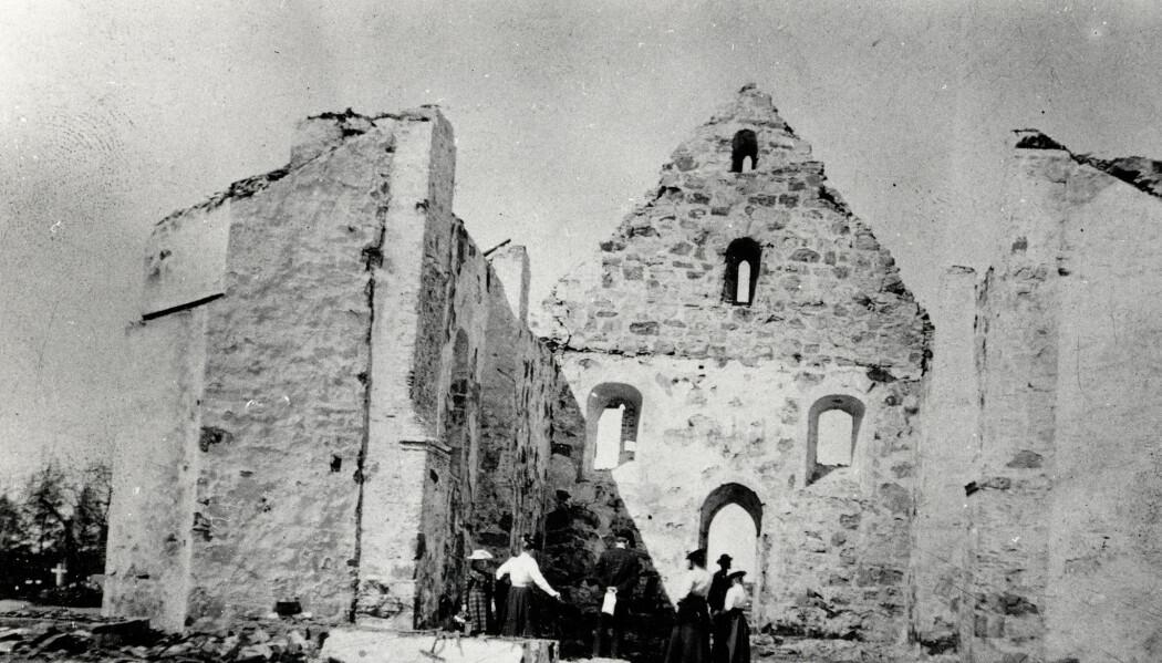Mennesker midt i ruinene av Øyestad kirke før den ble gjenoppbygd. (Foto: Riksantikvarens billeddatabase, kulturminnebilder.ra.no)